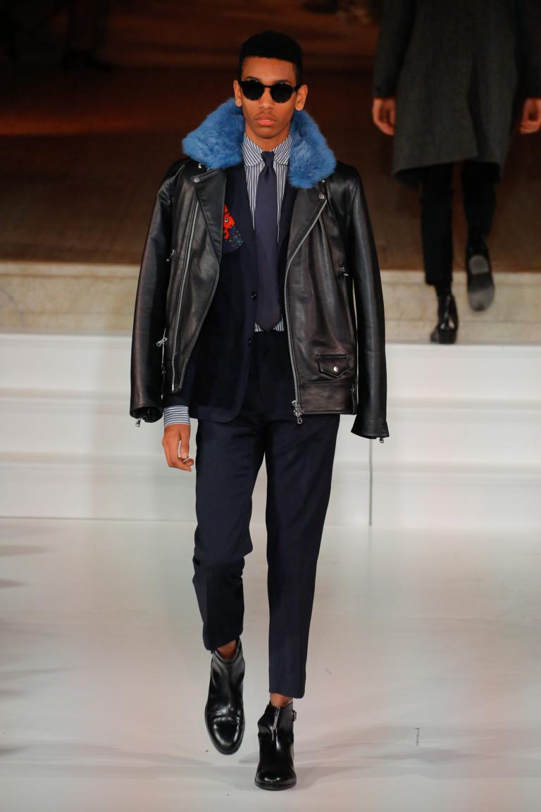 Черная мужская куртка с голубым воротником и укороченными черными брюками.