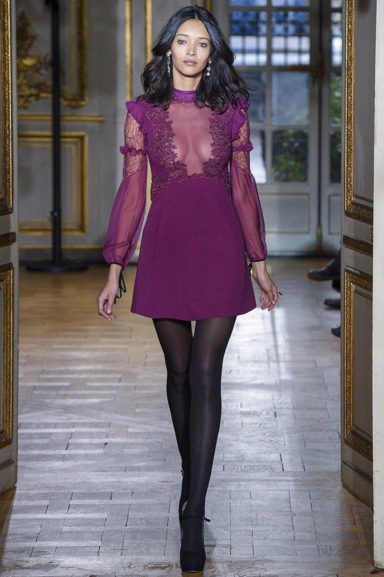 Фиолетового цвева платье с кружевным верхом и длинными кружевнми и прозрачными рукавами с черными чулками и туфлями.
