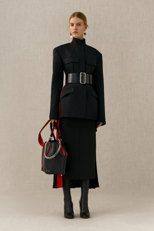 Сумка повторяющая цвет одежды черно-красный с короткой ручкой цепочкой и длинной кожаной ручкой красно-черного цвета.