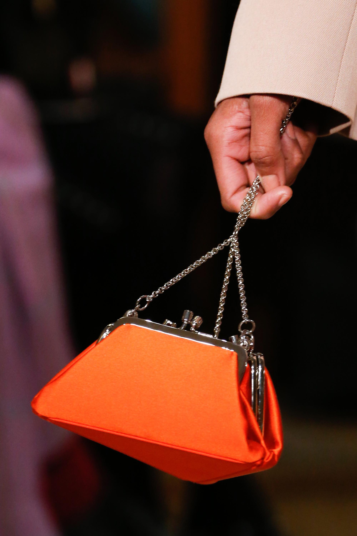 Сумка неординарной формы ярко оранжевого цвета с ручкой-цепочкой.